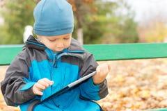 Weinig jongen die een tablet-PC met behulp van royalty-vrije stock afbeeldingen