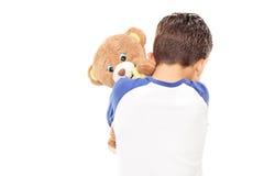 Weinig jongen die een teddybeer koesteren Stock Foto