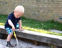 Weinig jongen die in een zandkuil spelen Stock Afbeelding