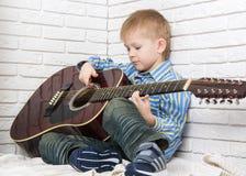 Weinig jongen die en de gitaar zitten spelen Stock Afbeelding