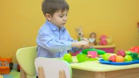 Weinig jongen die en de komkommer in kinderen` s ruimte spelen eten stock video