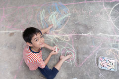 Weinig jongen die en door krijt op de activiteit van de grondkunst trekken kleuren royalty-vrije stock afbeeldingen