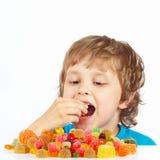 Weinig jongen die gekleurd geleisuikergoed op witte achtergrond eten stock foto's