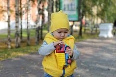 Weinig jongen die in gele kleren in haar handen houden een stuk speelgoed vrachtwagen royalty-vrije stock foto
