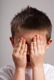 Weinig jongen die gezicht behandelt met handen stock afbeeldingen