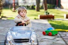 Weinig jongen die grote stuk speelgoed auto drijven, in openlucht Royalty-vrije Stock Afbeeldingen