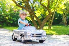 Weinig jongen die grote stuk speelgoed oude auto drijven, in openlucht stock afbeelding