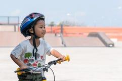 Weinig jongen die helmen dragen die fiets bevrijden stock foto