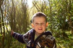 Weinig jongen die in het hout glimlacht Stock Foto