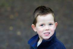 Weinig jongen die in het hout glimlacht Stock Afbeelding