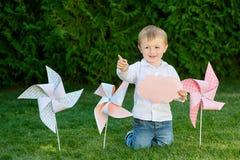 Weinig jongen die in het park op het gras met windmolens spelen stock fotografie