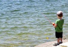 Weinig jongen die in het reservoir dichtbij Austin vissen stock foto's