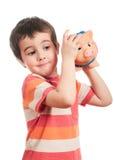 Weinig jongen die het spaarvarken schudt Royalty-vrije Stock Foto