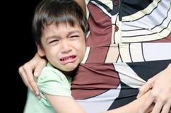 Weinig jongen die houdend zijn moeder zwarte achtergrond schreeuwen Stock Fotografie