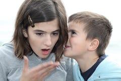 Weinig jongen die iets fluistert aan zijn zuster royalty-vrije stock foto