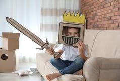 Weinig jongen die kartonpantser in woonkamer dragen royalty-vrije stock foto