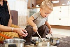 Weinig jongen die in keuken speelt Royalty-vrije Stock Foto's