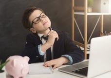 Weinig jongen die in kostuum over financiën denken royalty-vrije stock foto