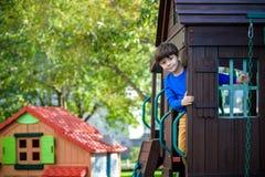 Weinig jongen die ladder op dia beklimmen bij speelplaats Het kind is 5 7 jaarleeftijd Kaukasisch, toevallig gekleed in jeans en  stock afbeelding