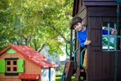 Weinig jongen die ladder op dia beklimmen bij speelplaats Het kind is 5 7 jaarleeftijd Kaukasisch, toevallig gekleed in jeans en  stock foto