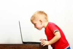 Weinig jongen die laptop de computer van PC thuis met behulp van Royalty-vrije Stock Afbeeldingen