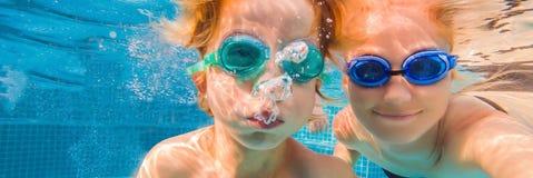 Weinig jongen die leren in een zwembad te zwemmen, moeder die de kindbanner, LANG FORMAAT houden royalty-vrije stock fotografie