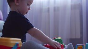 Weinig jongen die met auto's in stuk speelgoed garage spelen Voorraadlengte 4K stock video