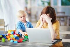 Weinig jongen die met bouw spelen blokkeert terwijl zijn moeder die aan computer werken Royalty-vrije Stock Fotografie