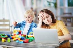 Weinig jongen die met bouw spelen blokkeert terwijl zijn moeder die aan computer werken stock fotografie