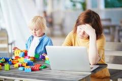 Weinig jongen die met bouw spelen blokkeert terwijl zijn moeder die aan computer werken royalty-vrije stock foto