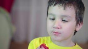 Weinig jongen die met bruin haar een aardbei eten Glimlachende en charismatische 4K stock video