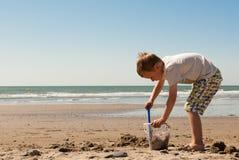 Weinig jongen die met emmer en zand op het strand spelen Royalty-vrije Stock Afbeeldingen