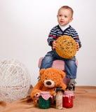 Weinig jongen die met garenballen spelen op een witte achtergrond stock afbeeldingen