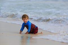 Weinig jongen die met golven op zandstrand spelen Stock Fotografie
