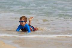 Weinig jongen die met golven op zandstrand spelen Stock Afbeeldingen