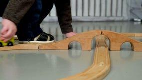 Weinig jongen die met houten spoorweg spelen stock videobeelden