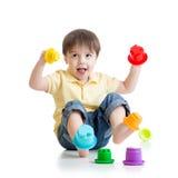 Weinig jongen die met kleurenspeelgoed spelen Stock Foto