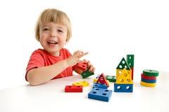 Weinig jongen die met kleurrijk blok spelen stock fotografie