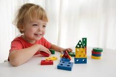 Weinig jongen die met kleurrijk blok spelen stock foto