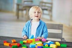 Weinig jongen die met kleurrijke plastic bouwblokken spelen Stock Foto's