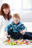 Weinig jongen die met kubussenmoeder het letten speelt op Royalty-vrije Stock Afbeelding