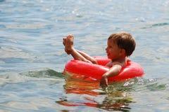 Weinig jongen die met rode buyoy ring zwemt Royalty-vrije Stock Fotografie