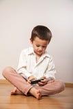 Weinig jongen die met smartphone spelen royalty-vrije stock fotografie