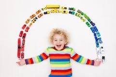 Weinig jongen die met stuk speelgoed auto's speelt Speelgoed voor Jonge geitjes stock fotografie