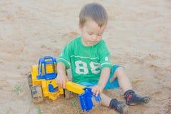 Weinig jongen die met stuk speelgoed graafwerktuig in het zand spelen Het kind zit stock afbeeldingen