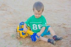Weinig jongen die met stuk speelgoed graafwerktuig in het zand spelen Het kind zit royalty-vrije stock foto's