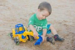 Weinig jongen die met stuk speelgoed graafwerktuig in het zand spelen Het kind zit stock afbeelding