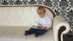 Weinig jongen die met tabletzitting spelen op bank stock videobeelden