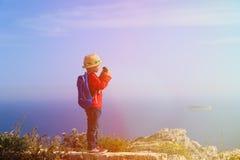 Weinig jongen die met verrekijkers in bergen wandelen Stock Foto