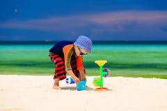 Weinig jongen die met water op zandstrand spelen Royalty-vrije Stock Foto's